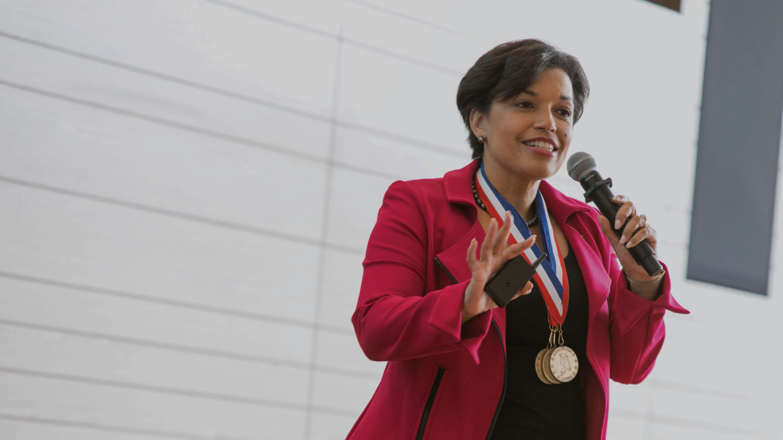 Bonnie St John speaking while wearing Olympic medals